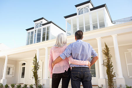 Family Standing in Front Of House Purchased From Realtor